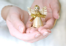 Little Angel - Decoration. Hands giving little straw angel. Shallow deph of field - focus is on the angel's face Royalty Free Stock Images
