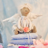 Little angel doll sitting on a pillow. Valentine`s day. Children`s toy hand made Stock Photos
