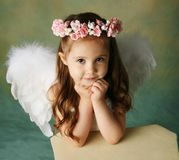 Little Angel Girl. Beautiful young girl wearing angel wings and flower halo with smile happy expression Stock Images