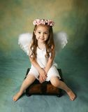 Little Angel Girl. Beautiful young girl wearing angel wings and flower halo with smile happy expression Stock Image
