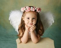 Little Angel Girl. Beautiful young girl wearing angel wings and flower halo with smile happy expression Royalty Free Stock Images
