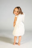 Little angel girl. Adorable four year old little girl, dressed as an angel in white with feather wings...standing, barefoot, looking back at the camera over her Royalty Free Stock Photography