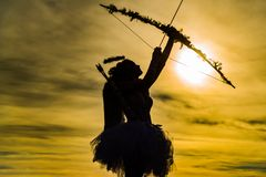 Little angel girl against sunny sky. Teen angel girl archer on sunset. Silhouette of a cupid. Side view of teen girl royalty free stock photos