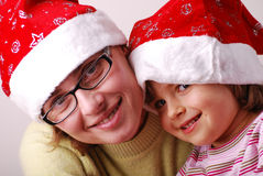 Little angel with mother. Little girl with mother with santa claus hat royalty free stock photo