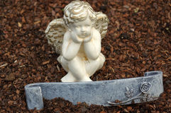 Little angel sculpture decorate in small garden with a sign in front it Stock Image