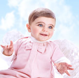 Little angel in the sky. Little angel in heaven, adorable baby girl with white wings on blue cloudy sky background, innocence and purity concept Stock Images