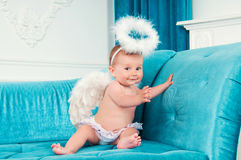Little angel smiling and happy sitting on the couch. Stock Images