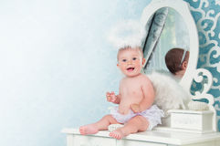 Little angel smiling and sitting on the dressing table Royalty Free Stock Photography
