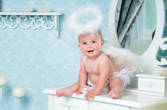 Little angel smiling and sitting on the dressing table Stock Photo