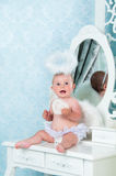 Little angel smiling and sitting on the dressing table Royalty Free Stock Photos