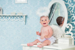 Little angel smiling and sitting on the dressing table Stock Image