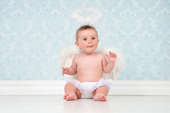 Little angel smiling and sitting on the floor. Stock Image