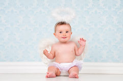 Little angel smiling and sitting on the floor. Royalty Free Stock Photos