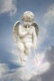 Little angel soars on a blue sky. Little angel statue soars on a blue sky with rays of magic light Stock Photo