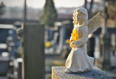 Little angel statue on a grave. Cemetery statue close up photo Royalty Free Stock Image