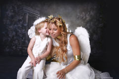 A little Angels Secret. Angelic Mother and Giggling Son telling her a secret royalty free stock images