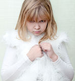 Little angry blond girl in white Royalty Free Stock Photo