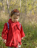 Little angry upset girl in a red jacket stands alone in the Stock Photos