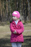 Little angry upset girl standing alone in the spring forest. Royalty Free Stock Photos