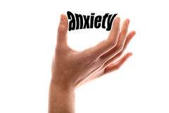Little anxiety. Color horizontal shot of a hand holding the word anxiety between two fingers royalty free stock photography