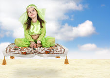 Little arabian girl sitting on flying carpet. With sky background Royalty Free Stock Photography