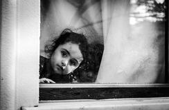 Little Arabic Kids On The Window - Turkey. Little Arabic kids looking through the window of their home in Cinarcik town of the country Turkey. Many immigrants Stock Photos