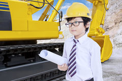 Little Architect with blueprint and excavator Stock Photo