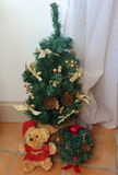 Little artificial Christmas tree and teddy bear Royalty Free Stock Image