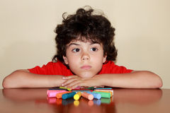 Little artist 2. A little boy who sits in front of figure made of colored crayons Royalty Free Stock Photos