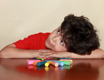 Little artist. Little boy lying leaning head in his hands to figure made of colored crayons Stock Photo