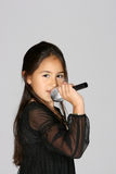 Little artist. Young girl with a microphone singing Royalty Free Stock Photos