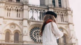 Little artist beret drawing near the Notre Dame in Paris, France. Stylish girl doing her hobby near famous church. Beautiful child developing talents stock footage