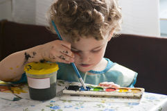 Little artist. Little boy drawing with a brush and paints on paper. He dip his brush into the blue paint. He has paint spots on face and arms. He concentrated on Stock Photos