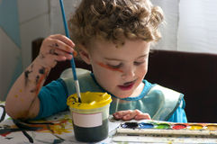 Little artist. Little boy drawing with a brush and paints on paper. He dip his brush into the water. He has paint spots on face and arms. He concentrated on the Royalty Free Stock Image