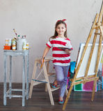 Little artist girl holding a paintbrush and looking over a canva Royalty Free Stock Photos