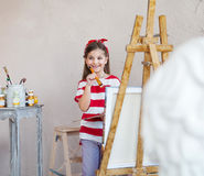 Little artist girl holding a paintbrush and looking over a canva Royalty Free Stock Photo