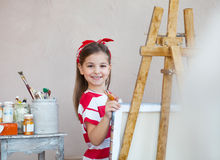 Little artist girl holding a paintbrush and looking over a canvas. On an easel. Concept of creativity and fun royalty free stock photo