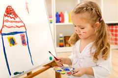 Little artist girl painting on large paper canvas Royalty Free Stock Photo