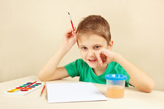 Little artist in green shirt going to paint colors Stock Image