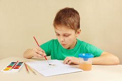 Little artist in green shirt painting with watercolors Stock Photos