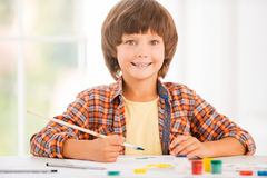 Little artist. Happy little boy relaxing while painting with watercolors sitting at the table Stock Image