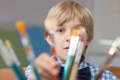 Little artist hiding behind paintbrushes Royalty Free Stock Photo