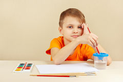Little artist in orange shirt going to paint colors Royalty Free Stock Photos