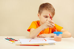 Little artist in orange shirt painting colors Stock Photography