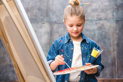 Little artist painting. Little female artist holding palette and painting picture on easel Stock Photo