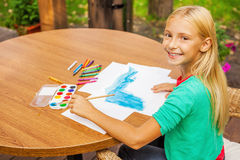 Little artist at work. Top view of cute little girl drawing something on paper and smiling while sitting at the table and outdoors Royalty Free Stock Photography