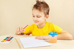 Little artist in yellow shirt going to paint colors Stock Photography