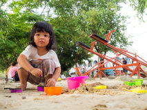 Little Asia girl sitting in the sandbox and playing with toy sand shovel bucket Stock Photo