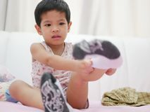 Little Asian baby being whiny while she is trying to put on socks royalty free stock photos