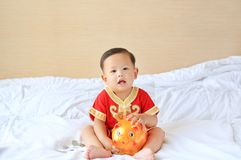 Little Asian baby boy in traditional Chinese dress with a piggy bank sitting on bed at home. Kid saving money concept.  stock image
